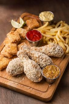 Angle élevé de planche à découper avec poulet frit et frites