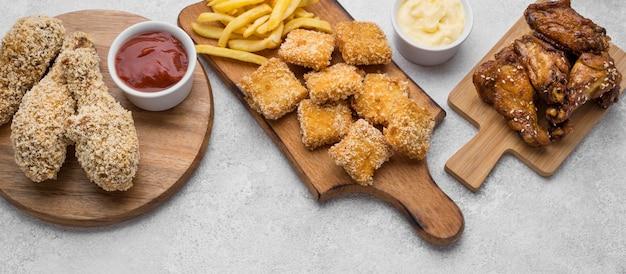 Angle élevé de planches à découper avec des pépites de poulet frit et des sauces
