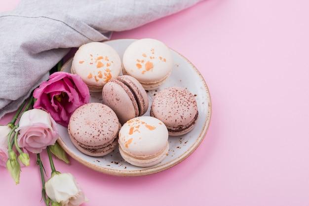 Angle élevé de plaque avec macarons et roses