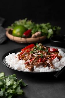 Angle élevé de plat asiatique traditionnel avec du riz et des herbes