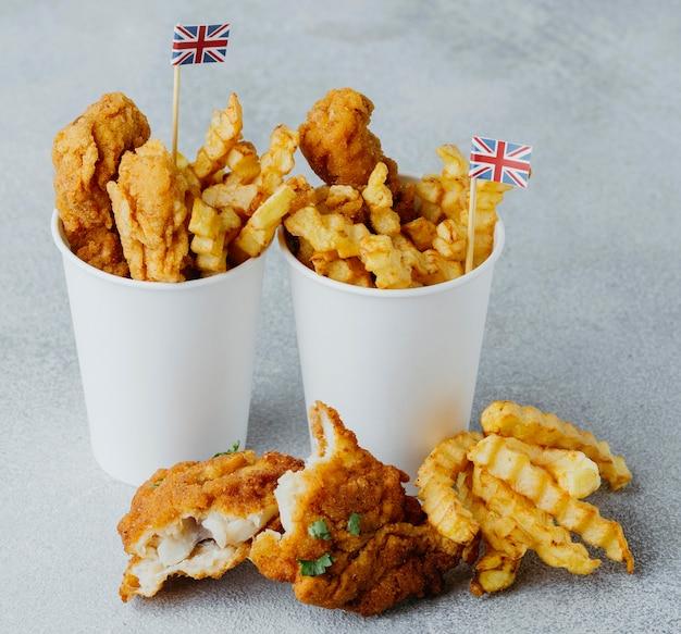 Angle élevé de poisson et frites dans des gobelets en papier avec des drapeaux de la grande-bretagne