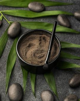 Angle élevé de poudre fine dans un bol avec des feuilles et des pierres