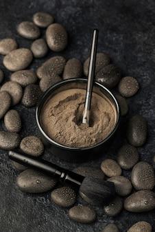 Angle élevé de poudre fine dans un bol avec des pierres et une brosse