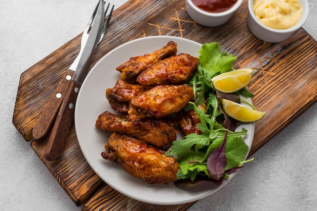 Angle élevé de poulet frit sur assiette avec couverts et sauce