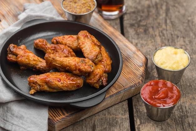 Angle élevé de poulet frit sur une assiette avec une variété de sauces et de boissons gazeuses