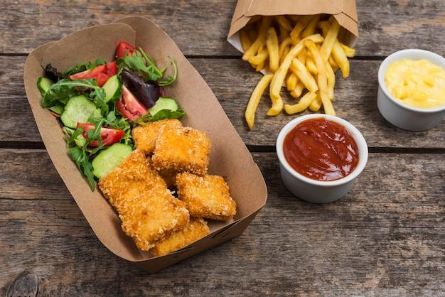 Angle élevé de poulet frit avec frites et salade