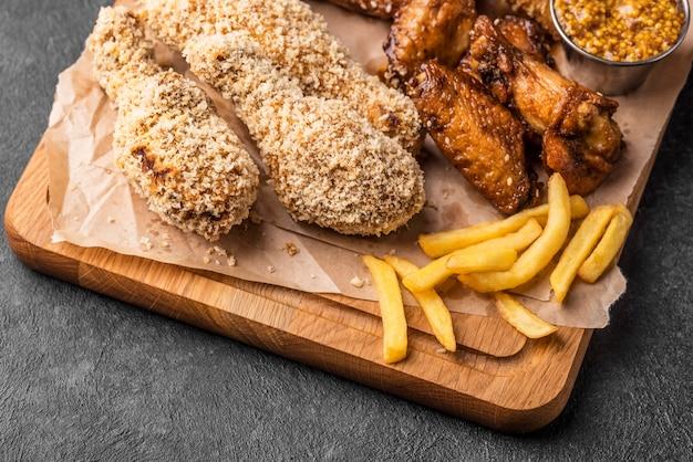 Angle élevé de poulet frit sur planche à découper avec frites