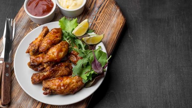 Angle élevé de poulet frit avec sauce et salade sur assiette