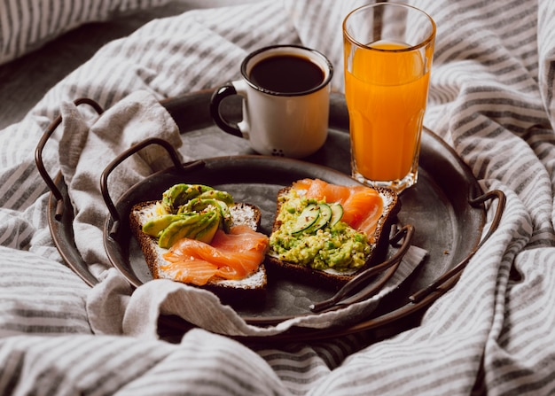Angle élevé de sandwichs au petit-déjeuner sur le lit avec avocat et saumon