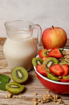 Angle élevé de sélection de céréales pour petit déjeuner dans un bol avec du lait et des fruits