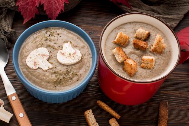Angle élevé de soupe aux champignons d'hiver dans une tasse et un bol avec des croûtons