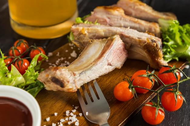 Angle élevé de steak avec tomates et bière
