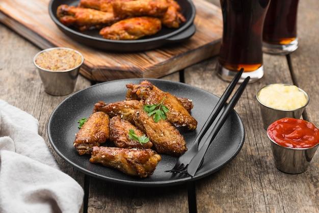 Angle élevé de table avec du poulet frit sur des assiettes et des boissons gazeuses