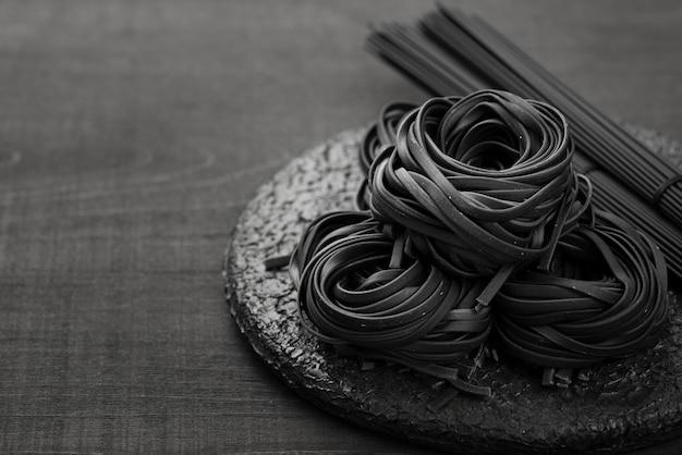 Angle élevé de tagliatelles noires sur une plaque avec des spaghettis