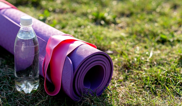 Angle élevé de tapis de sport et bouteille d'eau sur l'herbe