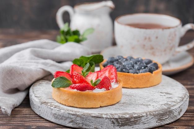 Angle élevé de tartes aux fruits avec thé et menthe