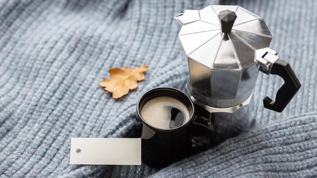 Angle élevé de tasse de café avec bouilloire sur pull