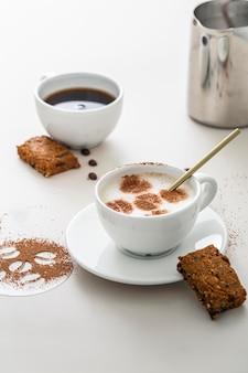 Angle élevé de tasses à café avec dessert et assiette