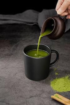 Angle élevé de thé matcha versé dans la tasse