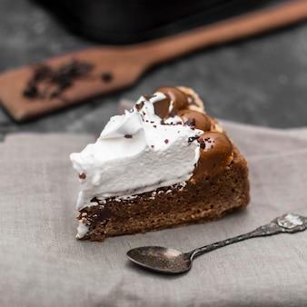 Angle élevé de tranche de gâteau avec une cuillère et un chiffon
