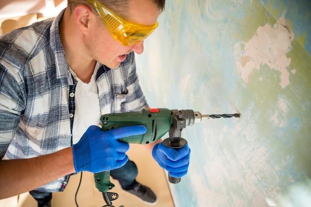 Angle élevé de travailleur avec marteau perforateur
