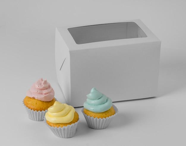 Angle élevé de trois petits gâteaux avec boîte d'emballage