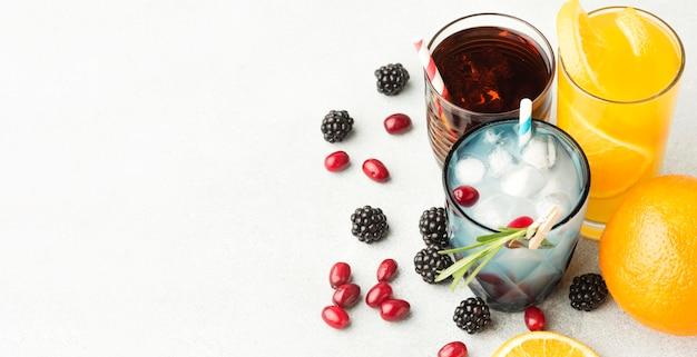 Angle élevé de verres à cocktail de fruits avec des pailles