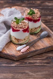 Angle élevé de verres avec du yaourt et des céréales sur planche de bois