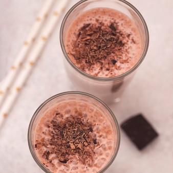 Angle élevé de verres de milkshake avec du chocolat et des pailles