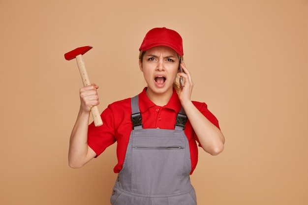 Angry young female construction worker wearing uniform and cap holding hammer talking on phone