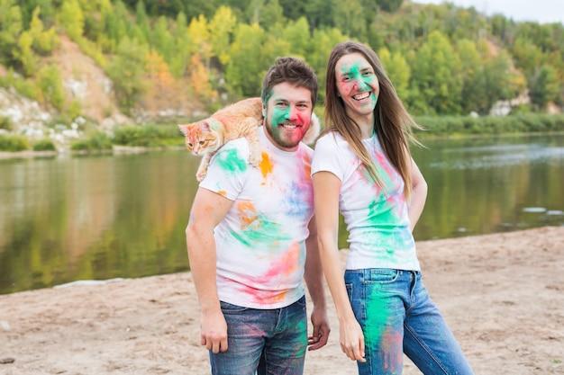 Animal de compagnie, tourisme d'été, festival holi et concept de nature - drôle homme et femme avec chat sur naturel