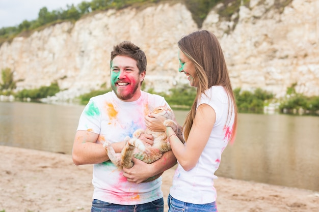 Animal de compagnie, tourisme d'été, festival holi et concept nature - homme et femme drôles avec chat sur fond naturel.