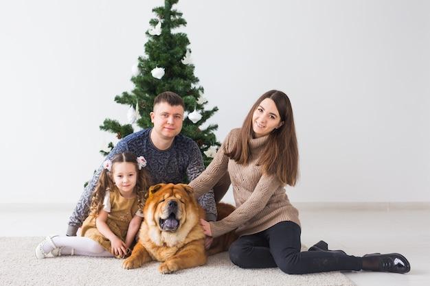 Animal de compagnie, vacances et concept festif - famille avec chien sont assis sur le sol près de l'arbre de noël.