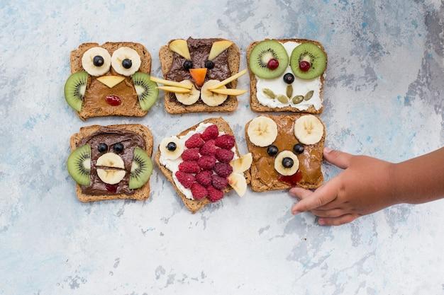 Animal drôle de petit déjeuner fait face à des toasts avec des tartinades