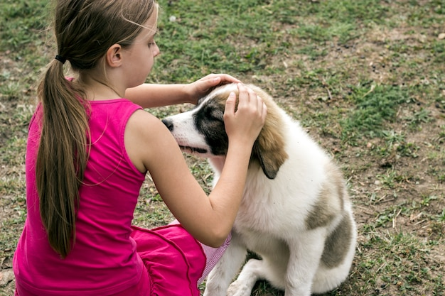 Animal love.mignonne petite fille dans le domaine caresse son beau chien
