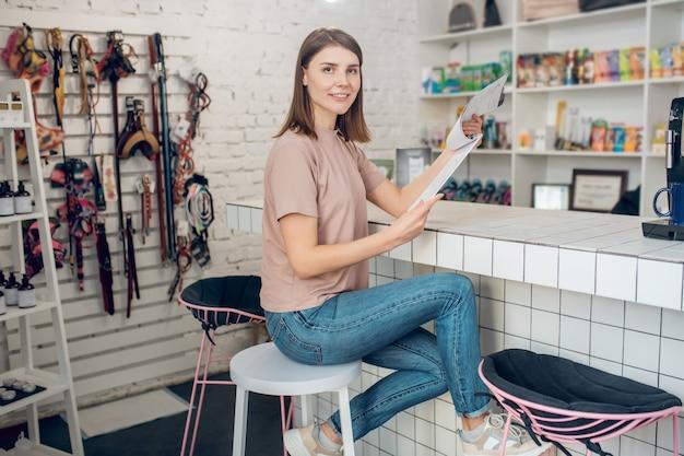 Animalerie. une fille dans un tshirt beige assis dans une animalerie et regardant à travers la liste de prix