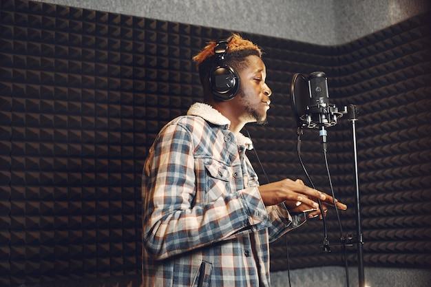 Animateur de radio faisant des gestes pendant l'enregistrement d'un podcast dans un studio de radio. l'homme africain répète dans un studio d'enregistrement.
