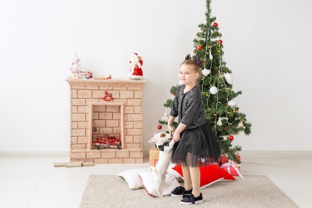 Animaux de compagnie, vacances et concept de noël - enfant fille jouant avec le chiot jack russell terrier près de l'arbre de noël.