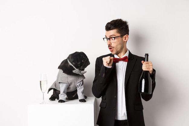 Animaux de compagnie, vacances d'hiver et concept du nouvel an. heureux jeune homme célébrant noël avec un mignon chien noir portant un costume de fête, chiot regardant le propriétaire, fond blanc.