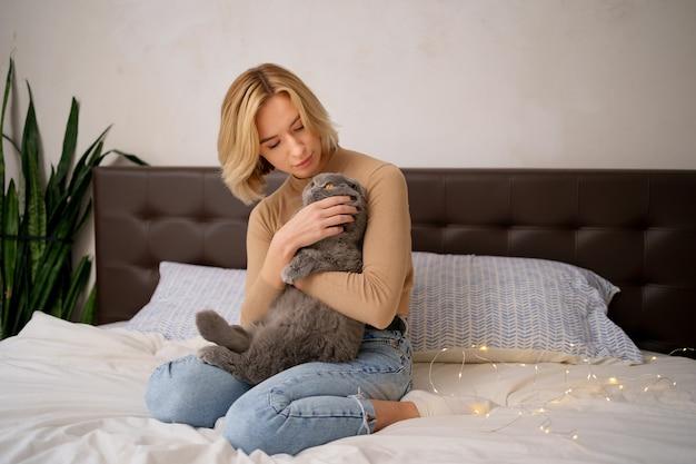 Animaux domestiques, matin, confort, repos et concept de personnes - heureuse jeune femme avec chat au lit à la maison