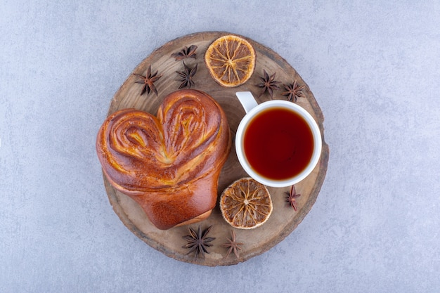 Anis étoilés, tranches de citron séchées, une tasse de thé et un petit pain sucré sur une planche de bois sur une surface en marbre