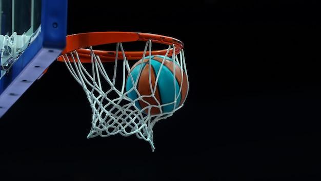Anneau de basket-ball avec un filet dans lequel le ballon vole sur un fond sombre