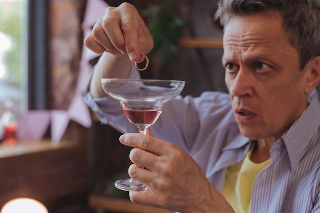 Anneau de cocktail. homme d'âge mûr sérieux tenant le verre et plaçant l'anneau dedans