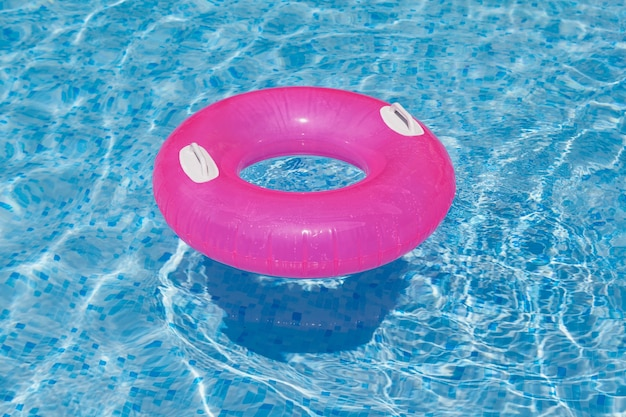 Anneau gonflable rose flottant dans la piscine vagues d'eau bleu clair