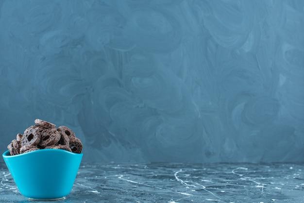 Anneau de maïs enrobé de chocolat savoureux dans un bol, sur la table en marbre.