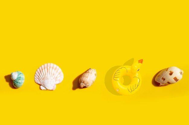 Anneau de piscine gonflable canard avec coquillages exotiques sur fond jaune.