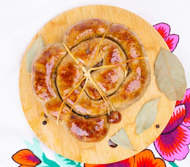 Anneau de saucisse frite sur une planche à découper en bois.