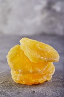 Anneaux d'ananas confits jaunes sur une surface de béton gris
