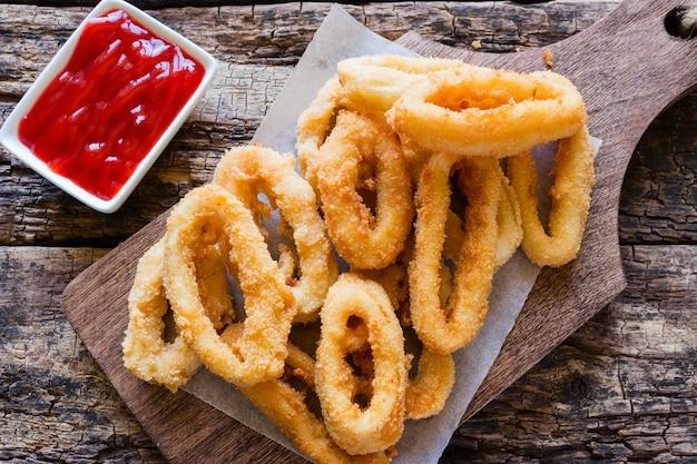 Anneaux de calamars frits dans une pâte sur une planche à découper
