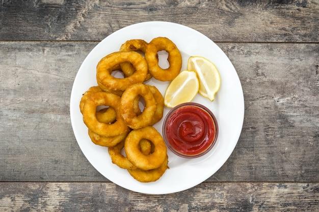 Anneaux de calamars frits avec du ketchup sur une surface en bois